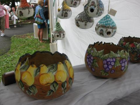 Three bowls and six bird feeders created with wood and paint with fruit designs on the bowls and bird designs on the bird feeders