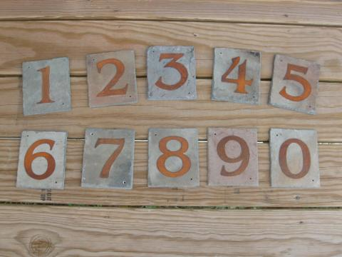 Square pieces of slate with golden numbers 1 through 0 stenciled on