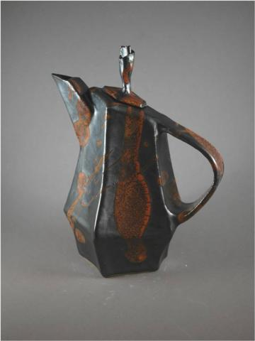 A teapot made out of clay that has an orange design down the sides to give it a rust appeal