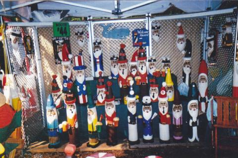 Santa Claus sculptures made out of wood wearing different holiday and ethnic clothing
