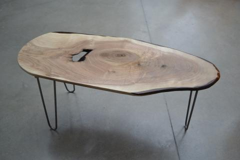 A table with a wood surface and black legs designed by Clayton Fant