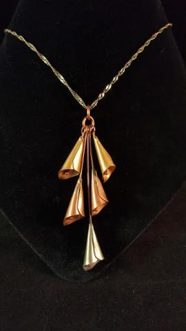 A gold necklace with long flower petals as the decorative