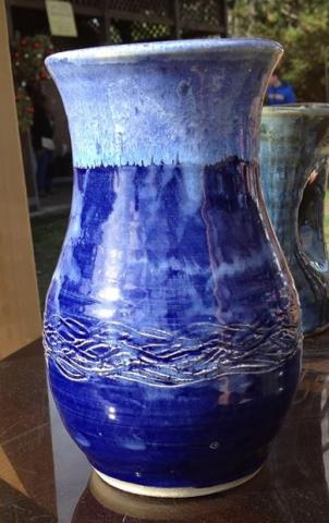 A clay pot with light blue painted on the top and dark blue painted from the middle to the bottom. There is a woven design etched into the bottom area of the pot