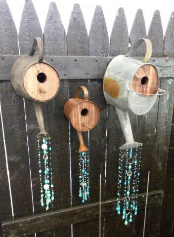 Three watering cans made out of wood and tin with beads glued to the ends to illustrate water coming out