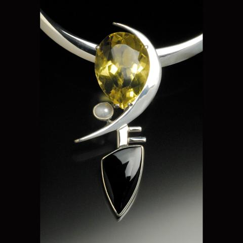 A gold, black and silver pendant