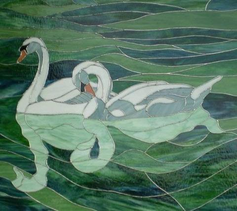 A stained glass portrait of two swans swimming together in a pond