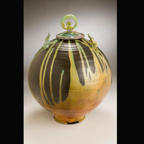A wide clay pot with a decorative lid on the pot that is painted brown with gold paint covering the bottom and giving the appearance of it dripping up