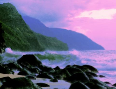 A photograph of the ocean waves crashing against rocks with a sunset and mountains in the background