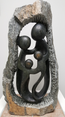 A sculpture of a four person family holding hands inside a stone circle