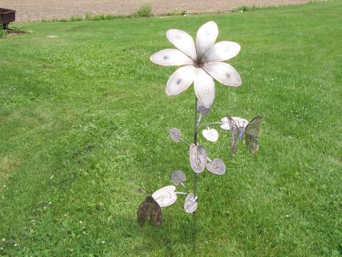 A bronze sculpture of a flower with two butterflys on the petals