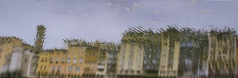 A photo of a blurry window, presumably caused by rain, overlooking a city street with buildings