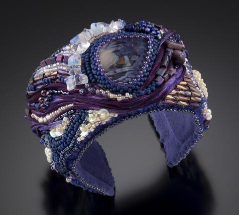 A ring made out of purple and white beads