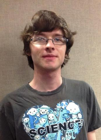 "A male student slightly smiling at the camera, wearing glasses and a tshirt that says ""heart science"""