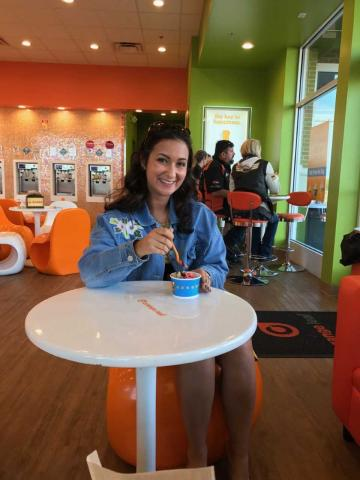 A smiling female posing with frozen yogurt while sitting in a colorful frozen yogurt shop