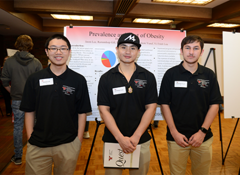 Three students standing infront of a posterboard