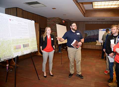 Two students explaining a poster to a group of people