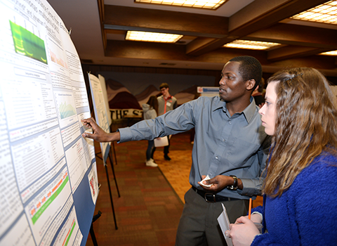 A student explaining his poster to a person
