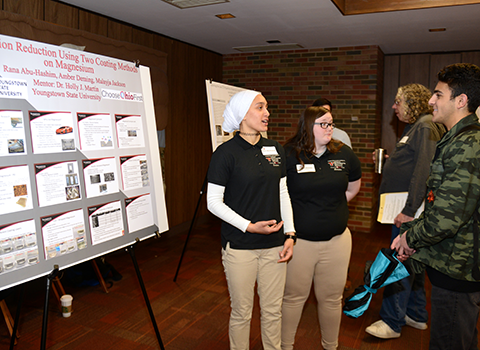 Two students explaining a poster to a person