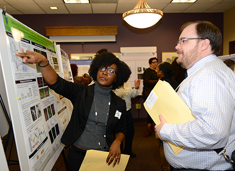 A student explaining her poster to person
