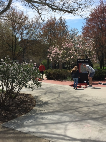 Students playing cornhole in the middle of campus on a sunny day