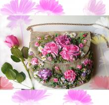 A tan purse with pink and purple flowers embroidered on the front
