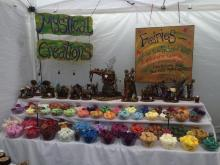 A photo of a vendor booth titled 'Mystic Creations' that has fairy sculpture, wax candles and tarts displayed