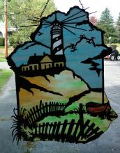 A glass piece hanging from a window with a haunted lighthouse portrait