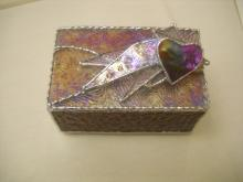 A glass jewelry box with a heart on top. The box is a purple and pink color