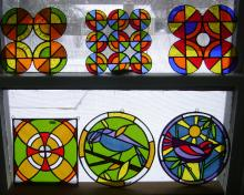 Glass art designs that feature reds, oranges and yellows with designs that are circular or birds and can hang from windows