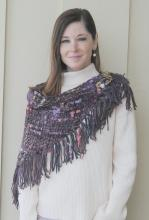 A woman with a tan turtleneck and handwoven purple and pink yarn scarf around her neck