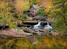 A photo of the mill at Mill Creek Park in Youngstown, Ohio during the fall with the leaves different colors