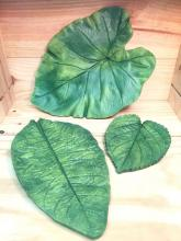 Three leaf plates that are painted green and vary in size from small to large