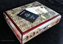 A box with a map of the world painted on the top with the words 'Enjoy the Journey' along the sides. A passport and envelope are glued to the top
