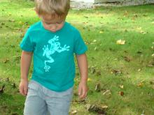 A green shirt worn by a child that is male with a light green frog on the front of the shirt
