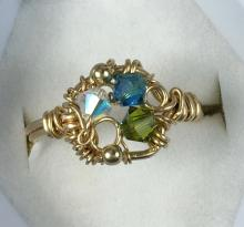 A gold ring with a white, blue and green jewel woven in