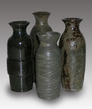 Four tall clay pots with different carved designs around the sides. Two are gray, one is gray and black and the fourth is all black