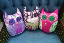 Three pillow owls propped up on a blue velvet chair. The owls range in a variety of colors between pink, brown, purple and green with flowers as eyes