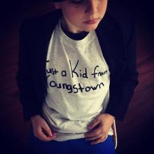 A young boy wearing a gray 'Just a kid from Youngstown' shirt