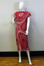 A full size mannequin wearing a woven red and white swirl dress that is cut at tea length and has short sleeves