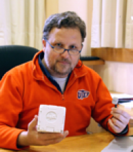 Male sitting at a desk looking directly at the camera, posing with equipment and wearing an orange pullover sweatshirt