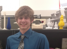 A smiling male student posing in a lab