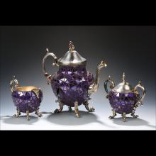 Two purple teapots with a purple teacup