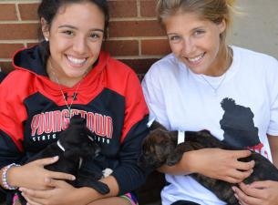 Two students holding puppies