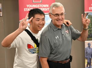 President Jim Tressel and a student in the Summer in America program pose for a photo during the con