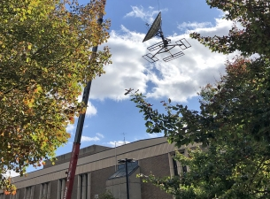 a giant crane removing old, outdated communications dishes and other equipment from the roof of Cus