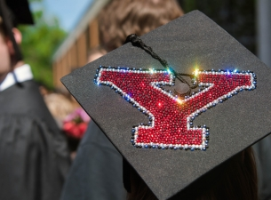 A graduation cap decorated with red rhinestones in the shape of Y.