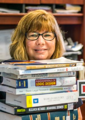A photo of Becky Varian, director of Center for Student Progress. Becky is posing with books