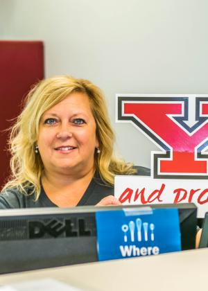 Chris Dilanni, a female worker, posing behind her computer but holding a Y and Proud sign while smiling at the camera