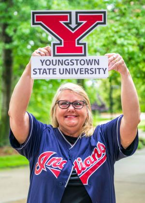 Debbie Moy, a female worker, posing outside with trees behind her. Wearing an Indians jersey while holding up a Youngstown State University sign