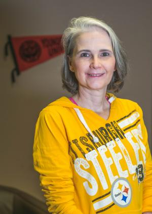 Gina McGranahan posing in her office wearing a yellow Pittsburgh Steelers sweatshirt